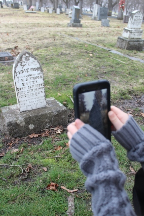 My daughter holding up my Google Pixel Phone to reveal the 3d Model of Susie Hope Estes' Headstone